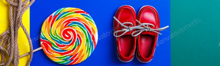 Banner with Small red boat shoes near big multi-colored lollipop and rope on colored background.