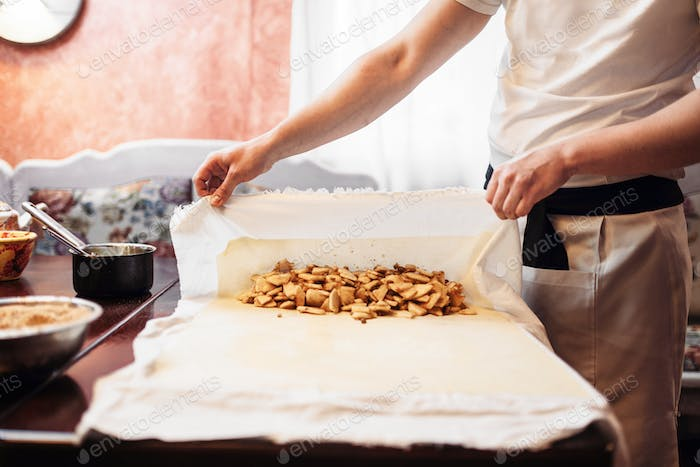 Chef wraps the filling into dough, apple strudel