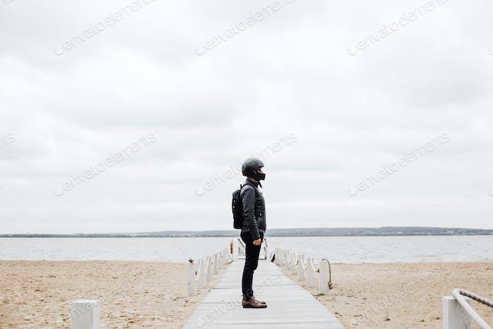 Mann stehend am Strand und mit Blick auf Wasser