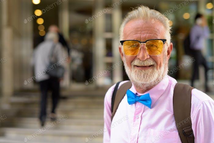 Handsome senior tourist man exploring the city of Bangkok, Thail