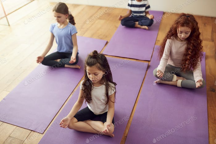 Group Of Children Sitting On Exercise Mats And Meditating In Yoga Studio