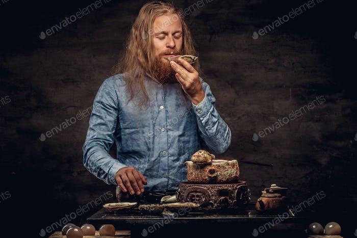 Бородатый рыжий мужчина в синей рубашке готовит чай
