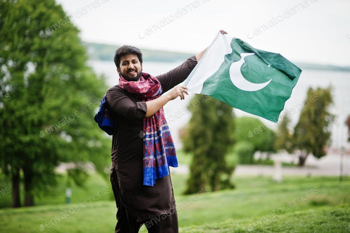Pakistani man wear traditional clothes hold flag of Pakistan.