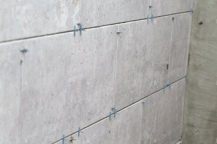 Tiles installation with spacers between ceramic tiles