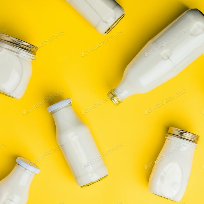 Various bottles of milk on yellow background