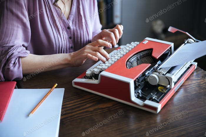 Authoress sitting at the table and typing on typerwriter indoors