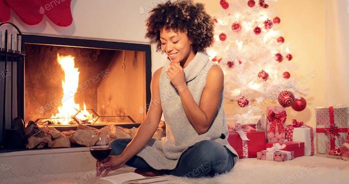 Smiling young woman enjoying a book at Christmas