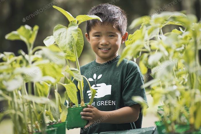 Ein Junge mit jungen Pflanzen in einem Pflanzengarten.