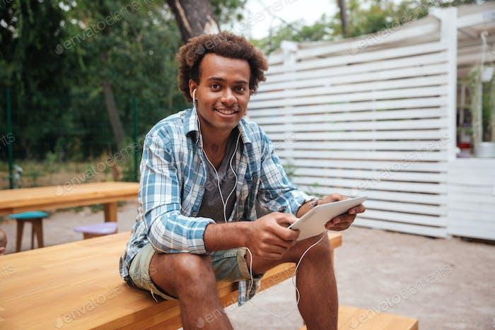 Fröhlicher afrikanischer junger Mann Musik von Tablet hören