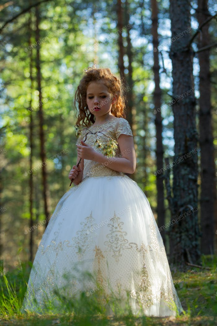 Little girl walks in a summer forest in a dress