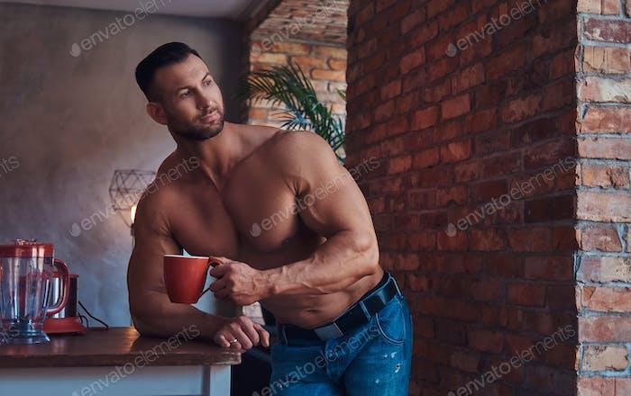 Großer, stilvoller, hemdloser Bodybuilder in Jeans gekleidet, stehend in einem Raum mit einem Loft-Interieur.