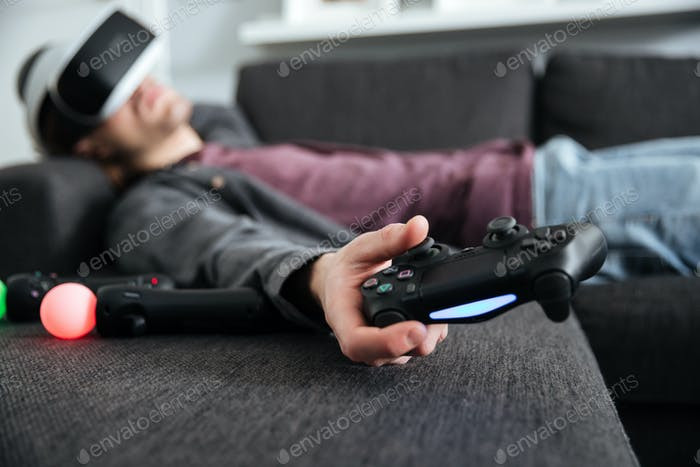 Man lies on sofa wearing 3d glasses holding joystick.