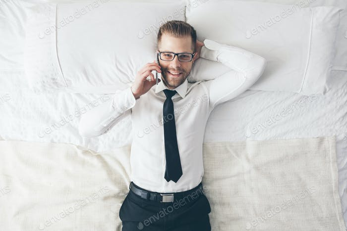 Top view. Handsome businessman with glasses on bed calling from his phone