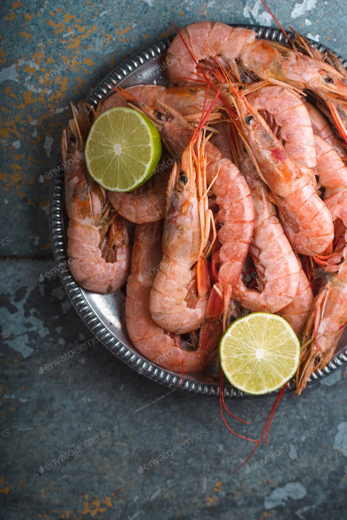 Large shrimps and lime on a tin plate