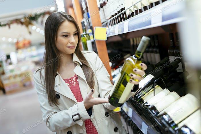 Mujer que decide qué vino comprar
