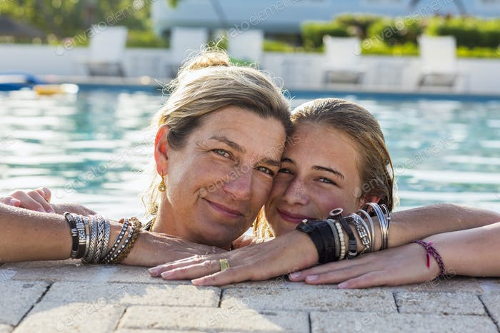 mother and her 13 year old daughter in pool smiling