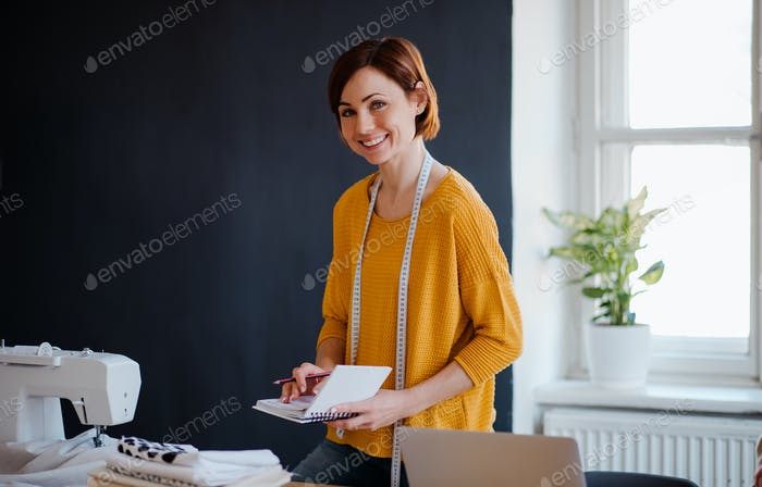 Young creative woman in a studio, writing. A startup of tailoring business.