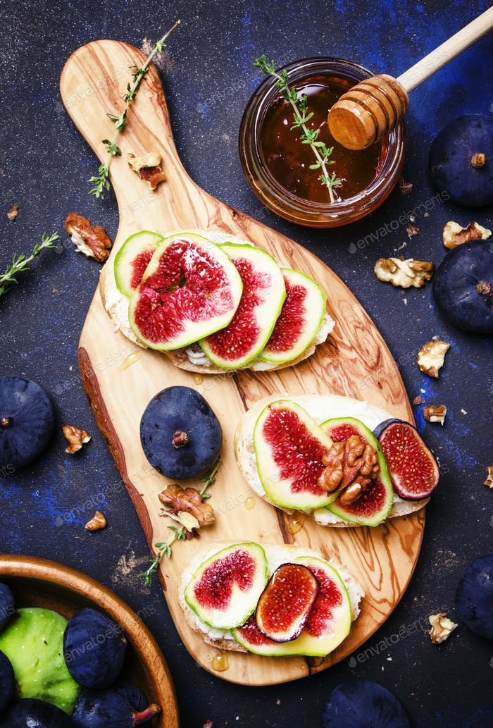 Sandwiches with cottage cheese, blue figs, thyme and honey, top view