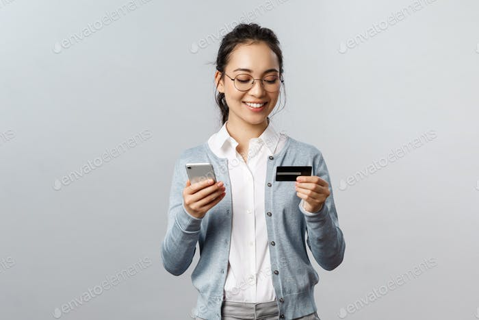Technology, online and mobile lifestyle concept. Cheerful relaxed asian housewife, employee working