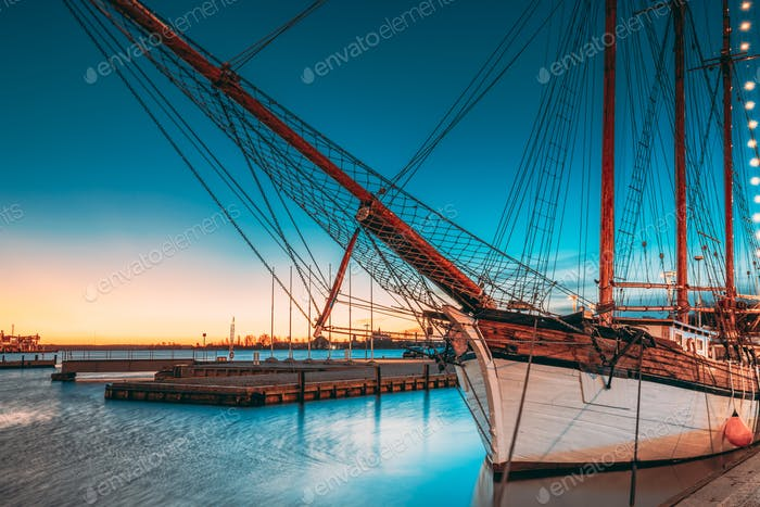 Helsinki, Finland. Old Wooden Sailing Vessel Ship Schooner Is Moored To City Pier, Jetty. Lighting