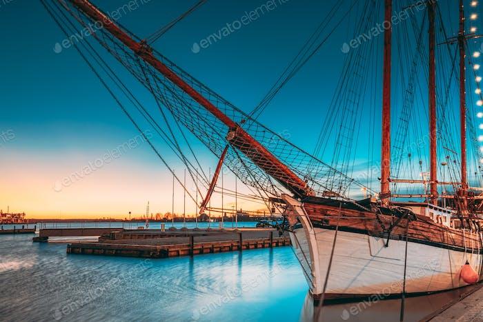 Helsinki, Finland. Old Wooden Sailing Vessel Ship Schooner Is Moored To City Pier, Jetty. Lighting