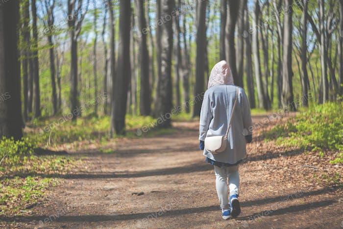 Mujer joven caminando sola en el bosque de principios de primavera