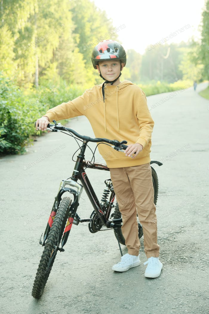 Happy youngster in yellow hoodie, beige pants, white sneakers and helmet