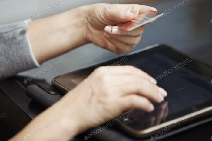 Human hand with digital tablet and credit card