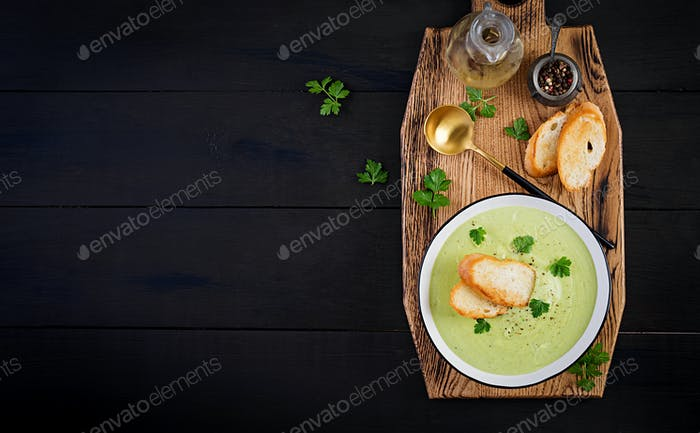 Homemade broccoli cream soup with croutons in white bowl