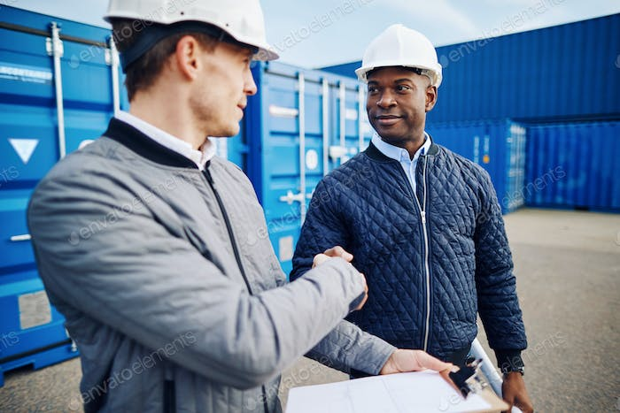 Engineers standing in a shipping yard smiling and shaking hands