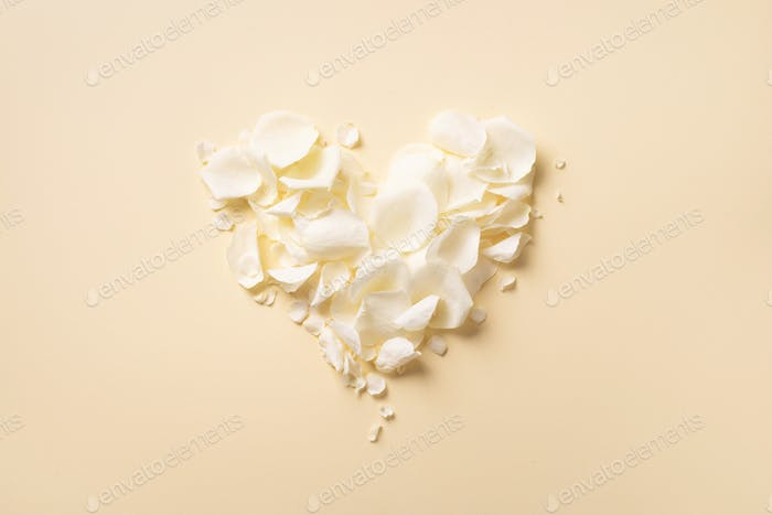 Heart made of white rose petals on pastel yellow background. Top view, flat lay. Love and romantic