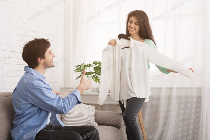 Young woman showing new shirt to husband