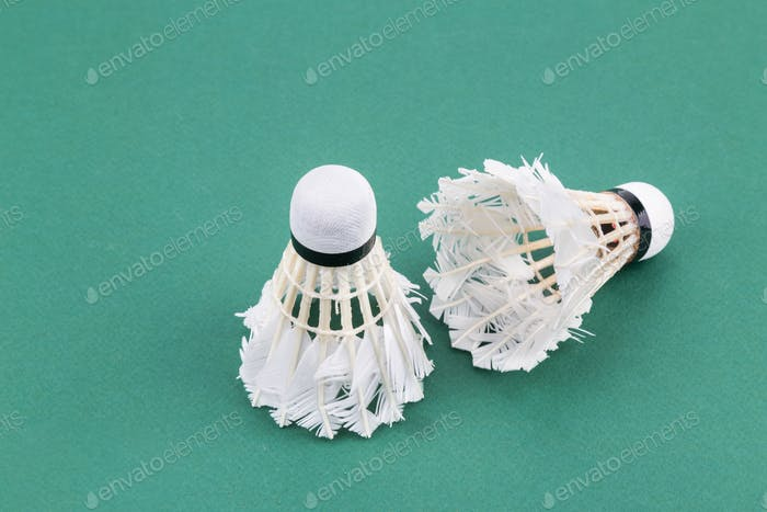 Two worned out used badminton shuttlecock  on green court mat