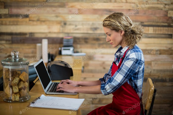 Waitress sitting at counter and using laptop in café