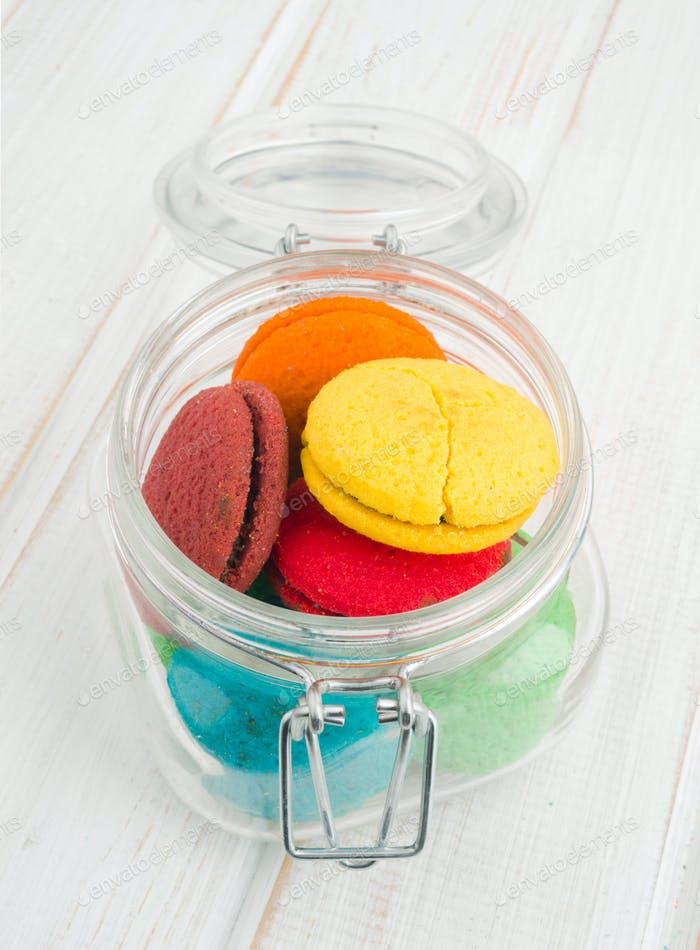 vertical colorful cookies in crystal flask on wood