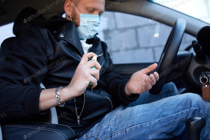 Mann in Schutzmaske sitzt im Auto, Sprühen Hände antibakterielle Desinfektionsspray