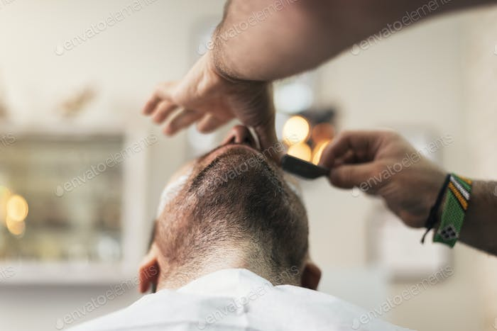 Young Bearded Man Getting Beard Haircut With A Razor By Barber.