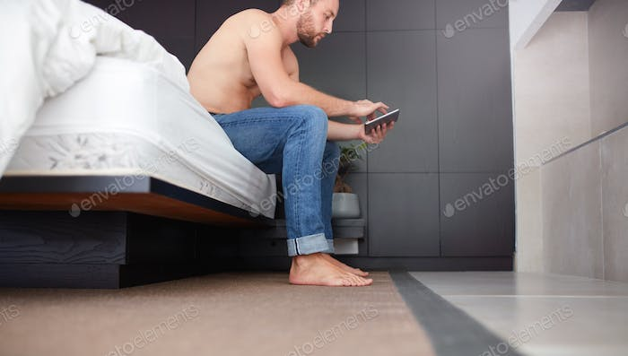 Young man sitting on bed using digital tablet