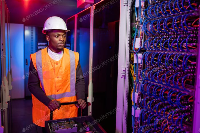 Data center electrician pushing cart with tools