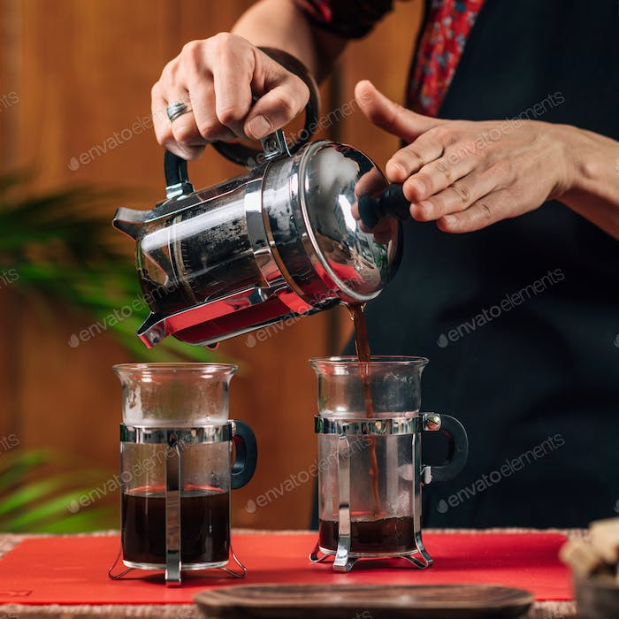 French Press Coffee. Barista Pouring French Press Coffee