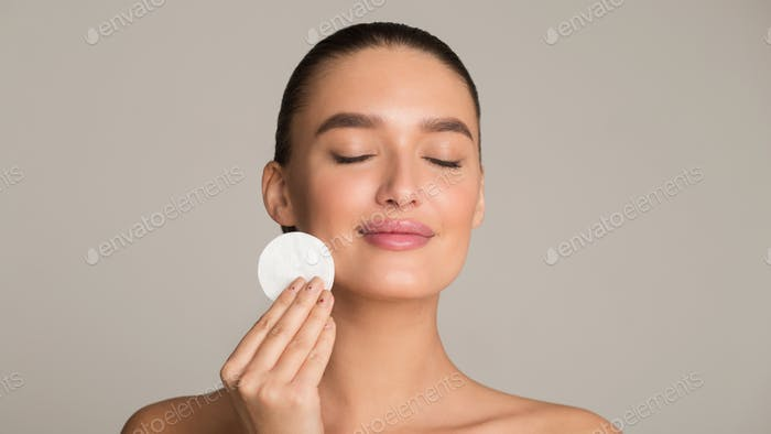 Daily skincare routine. Girl removing make up with cotton pad