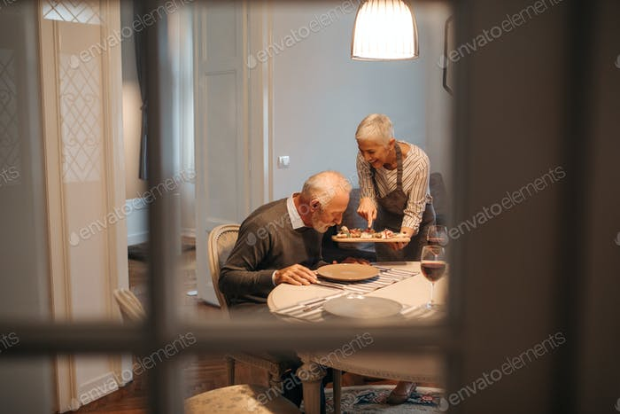 Happy elderly couple enjoying dinner at home