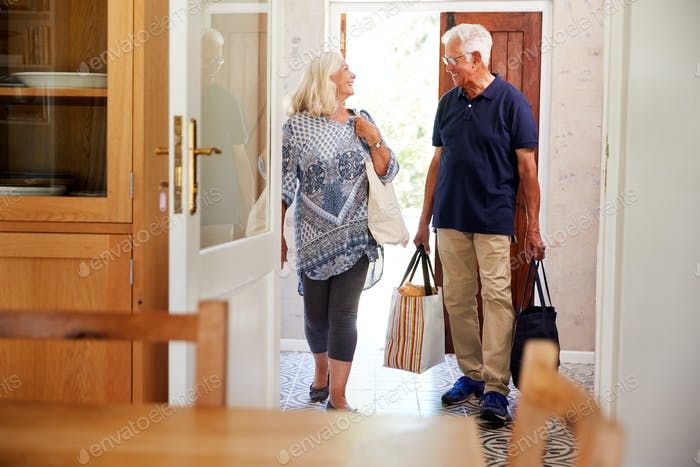 Senior Couple Returning Home From Shopping Trip Carrying Grocery Bags Through Kitchen