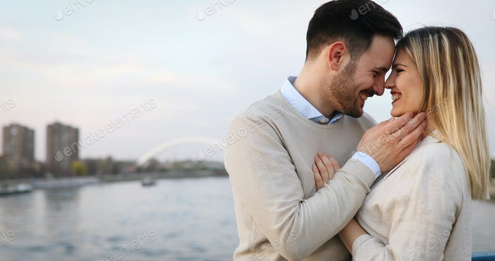Happy couple in love hugging and smiling outdoor