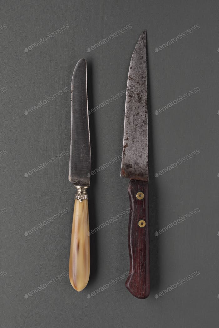 old battered knifes sorted on gray background