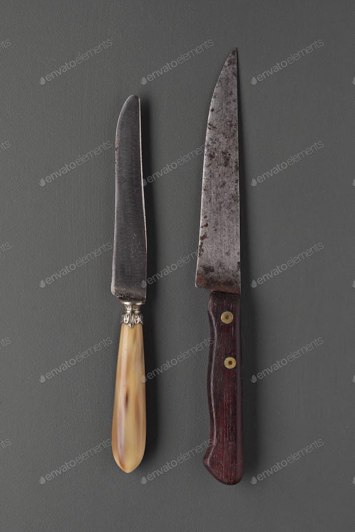 alte zerschlagene Messer sortiert auf grauem Hintergrund