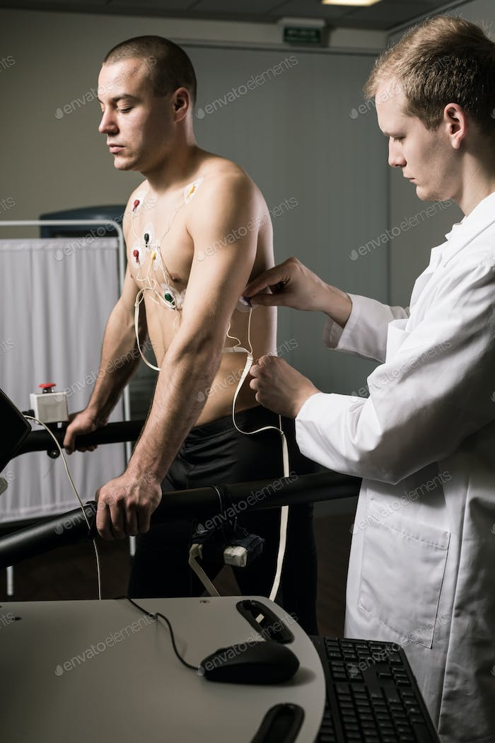Athletic man with cardiogram electrodes
