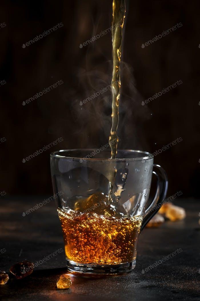 Schwarzer Tee in Glas gießen