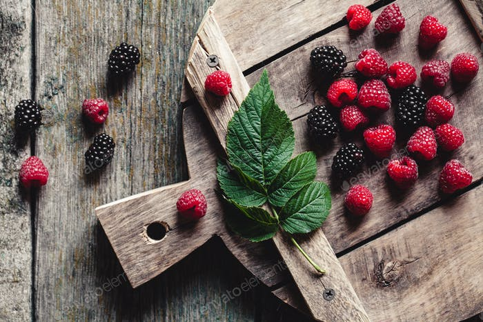 blackberries and raspberries on a cutting board. wooden background, vintage style