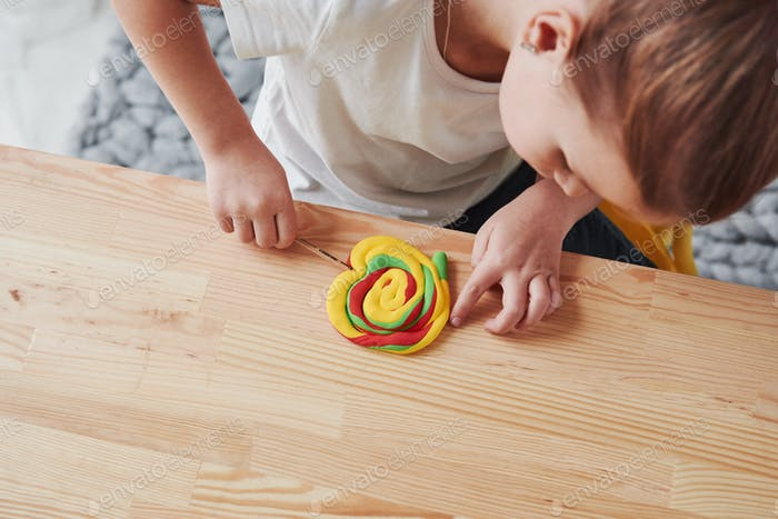 Children playing with colored plasticine on the wooden table at home